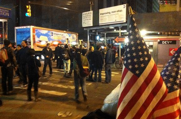 Caption: In this image made using a cell phone, Occupy Wall Street protesters are ordered to leave Zuccotti Park, their longtime encampment in New York, early Tuesday, Nov. 15, 2011. At about 1 a.m. Tuesday, police handed out notices from the park's owner, Brookfield Office Properties, and the city saying that the park had to be cleared because it had become unsanitary and hazardous. Protesters were told they could return, but without sleeping bags, tarps or tents. (AP Photo/Karly Domb Sadof)