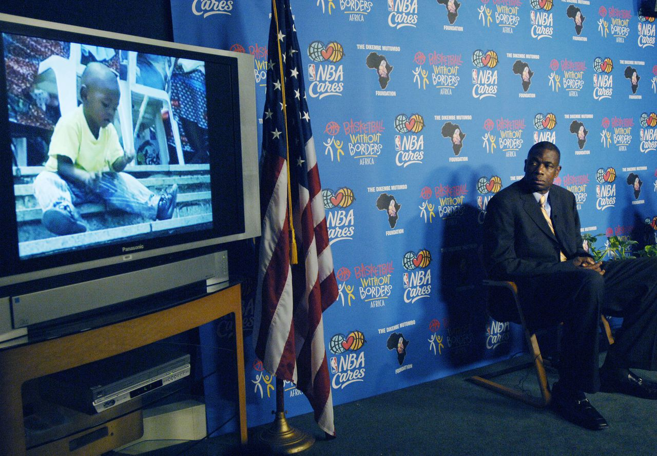 Dikembe Mutombo vorige week op een persconferentie in New York, terwijl hij een video bekijkt over 'zijn' nieuwe ziekenhuis in Kinshasa. Foto AFP Houston Rockets basketball star Dikembe Mutombo (R) watches a video about a 300-bed hospital he helped build in his hometown of Kinshasa, Democratic Republic of Congo, at a press conference, 16 August, 2006, in New York. The Biamba Marie Mutombo Hospital and Research Center, named after the player's mother, will open in September and has attracted support from the National Basketball Association (NBA) and NBA players. AFP PHOTO/Stan HONDA