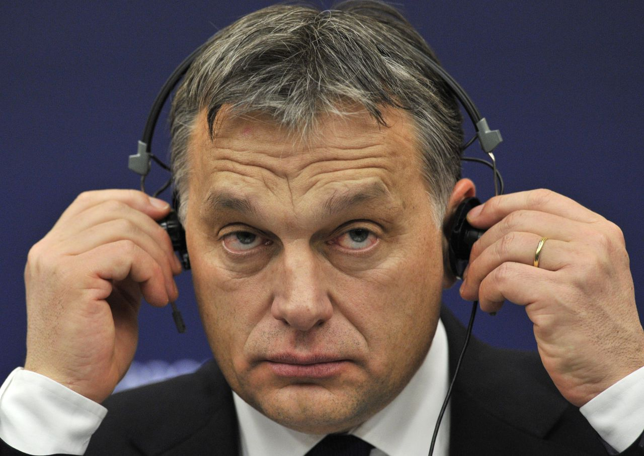 Hungarian Prime Minister Viktor Orban checks his headphones during a press conference on January 18, 2012 at the European Parliament in Strasbourg. Orban has told EU authorities he will modify controversial laws which are the subject of legal action against Budapest launched by the European Commission, the executive chief said on January 18. AFP PHOTO GEORGES GOBET