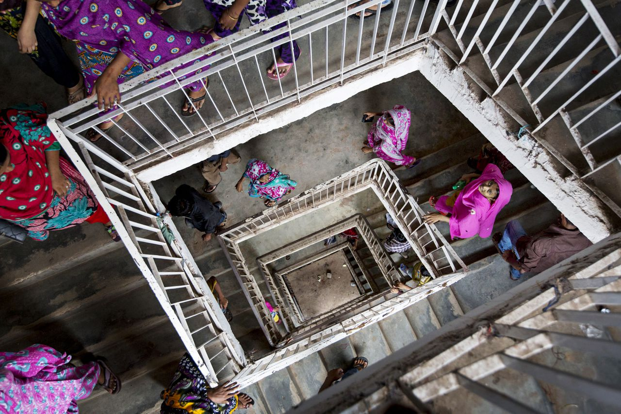 Workers leave a building that houses garment factories on their lunch break in Dhaka, Bangladesh, on Monday, April 29. The factories produce clothing for export. Photo/Jeff Holt