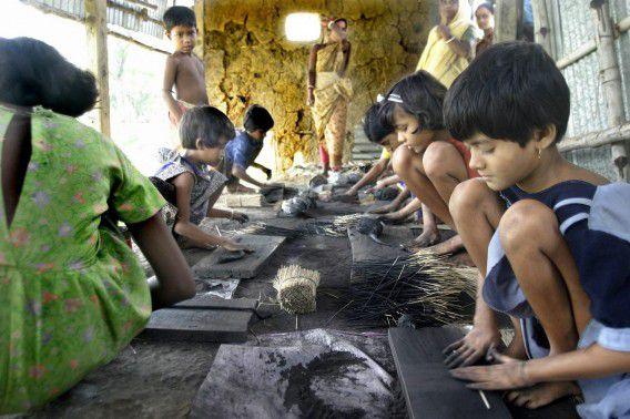 Kinderen in India aan het werk om wierookstokjes te maken; voor het maken duizend stokjes krijgen ze maar vijf Indiase roepies (zeventig eurocent).