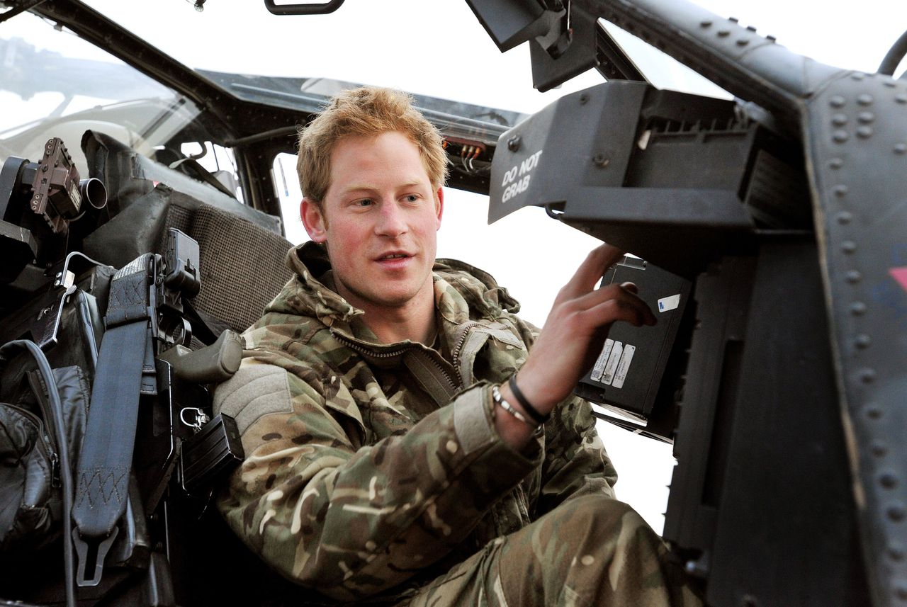 This picture taken on December 12, 2012 shows Britain's Prince Harry (R) makes his early morning pre-flight checks at the British controlled flight-line at Camp Bastion in Afghanistan's Helmand Province, where he was serving as an Apache Helicopter Pilot/Gunner with 662 Sqd Army Air Corps. Britain's Prince Harry confirmed he killed Taliban fighters during his stint as a helicopter gunner in Afghanistan, it can be reported after he completed his tour of duty on January 21, 2013. AFP PHOTO / POOL / JOHN STILLWELL