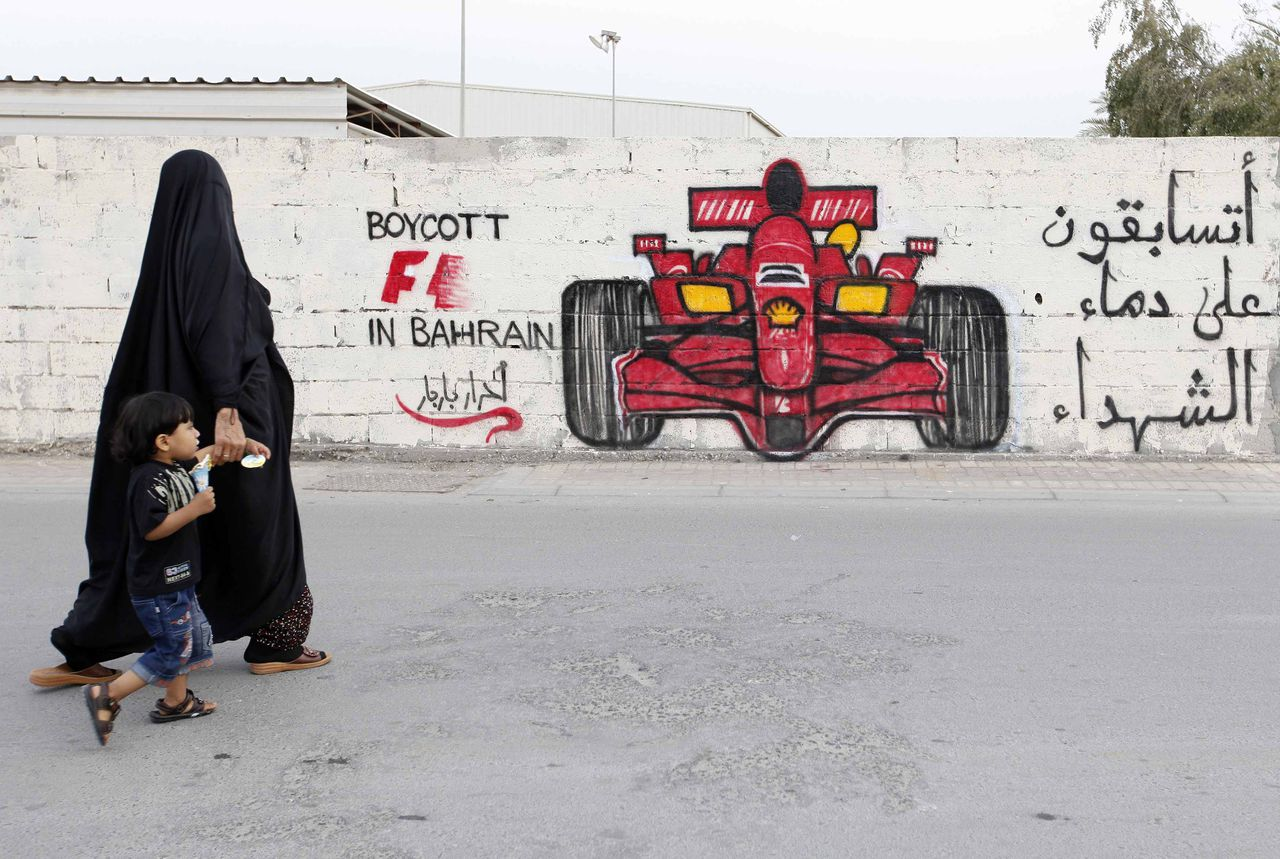 """A woman and her child pass in front of anti-Formula One graffiti in the village of Barbar, west of Manama in this April 5, 2012 file photo. Anti-government protesters in Bahrain are planning """"days of rage"""" directed at this weekend's Formula One Grand Prix, while security forces have rounded up dozens of activists in a clampdown on the opposition in the Gulf Arab nation.The graffiti reads, """"Boycott F1 in Bahrain, you will race on the blood of martyrs."""" Picture taken April 5, 2012. To match BAHRAIN-GRANDPRIX/PROTESTS REUTERS/Hamad I Mohammed/Files (BAHRAIN - Tags: CIVIL UNREST POLITICS SPORT MOTORSPORT)"""