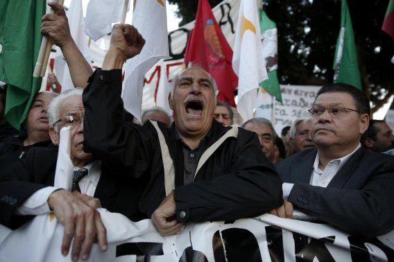 Demonstranten schreeuwen buiten het parlementsgebouw van Cyprus tegen het reddingsplan om het eiland er weer bovenop te krijgen.