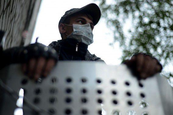 Een pro-Russische activist staat bij een barricade buiten het door separatisten bezette politiegebouw in Slavjansk.