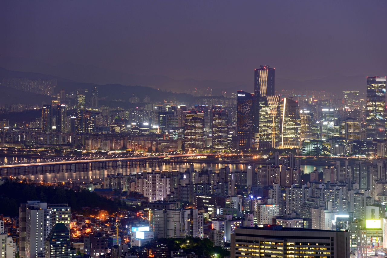"""A photo taken on May 9, 2014 shows a general view of the Seoul city skyline at dusk. The global cost of securing a clean energy future is rising by the year, the International Energy Agency (IEA) warned on May 12, 2014, estimating that an additional 44 trillion USD of investment was needed to meet 2050 carbon reduction targets. Releasing its biennial """"Energy Technology Perspectives"""" report in Seoul, the agency said electricity would increasingly power the world's economies in the decades to come, rivalling oil as the dominant energy carrier. AFP PHOTO / Ed Jones"""