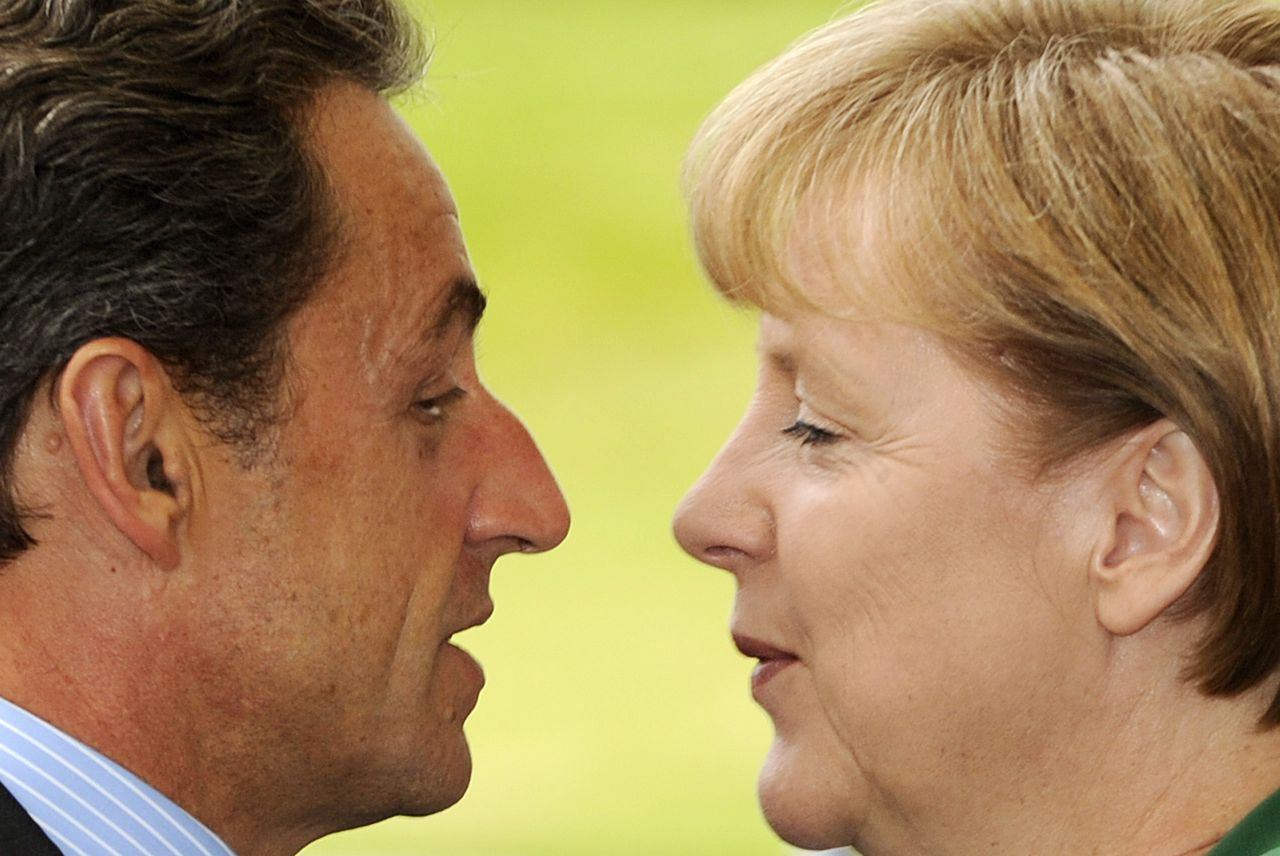 German Chancellor Angela Merkel greets French President Nicolas Sarkozy on July 20, 2011 in the courtyard of the Chancellory in Berlin, prior to talks one day ahead of a pivotal summit of heads of state and government in Brussels aimed at a sealing a second Greek bailout. Merkel and Sarkozy are confident they can agree in talks a common position for the eurozone summit, her spokesman said. TOPSHOTS/AFP PHOTO / ODD ANDERSEN