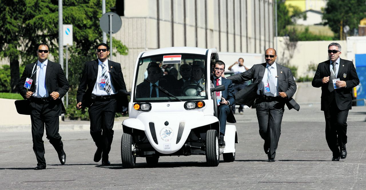 Security guards run alongside the electric car of Egypt's President Hosni Mubarak as he arrives for a round table meeting of the G8, G5 and Egypt at the G8 summit in L'Aquila, Italy on Thursday, July 9, 2009. Leaders of the exclusive club of eight industrialized nations open up their forum Thursday to the five fastest developing market economies in which they will discuss the economy, climate change and development aid. (AP Photo/Markus Schreiber, Pool)