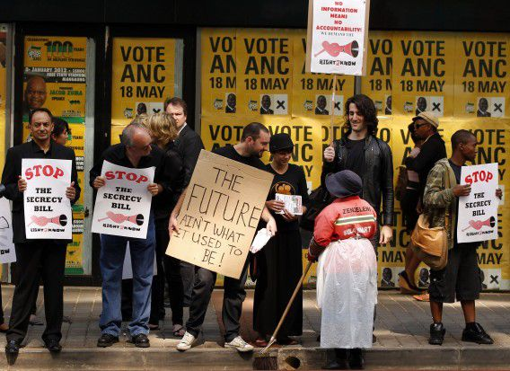 Members of the media and protesters chat to a worker outside the ruling African National Congress (ANC) headquarters, during a protest against the passing of new laws on state secrets in Johannesburg, November 22, 2011. South Africa's parliament is set to pass new laws his week that have been widely criticized as attempts to muzzle media and intimidate whistle blowers who would face stiff prison sentences for releasing classified documents. The measures, to be voted on in parliament on Tuesday, come amid growing concerns of cronysim in President Jacob Zuma's government, which has been hit by a barrage of embarrassing media reports about corruption in its ranks. REUTERS/Siphiwe Sibeko (SOUTH AFRICA - Tags: POLITICS CIVIL UNREST MEDIA)