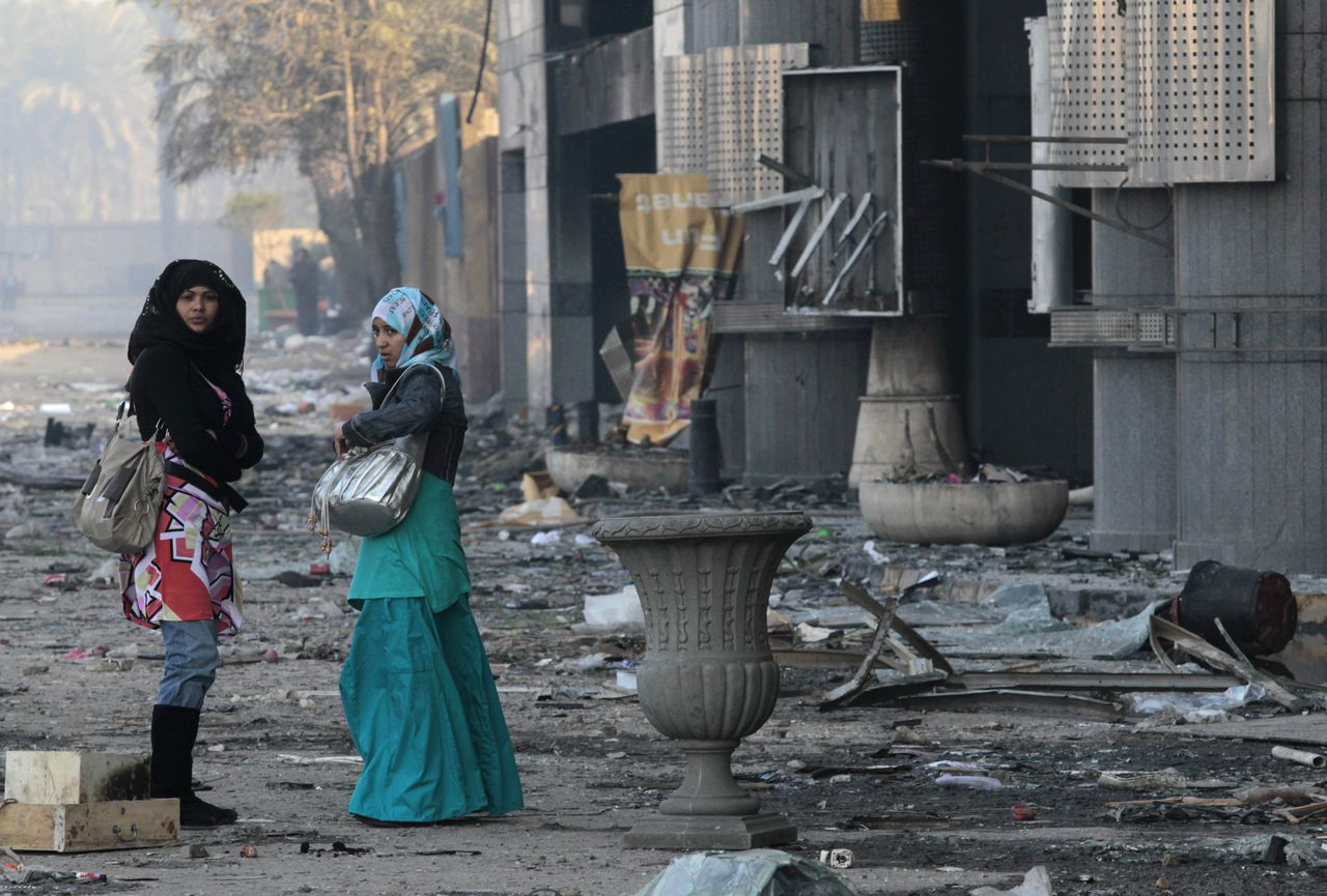 Women walk past a damaged shopping center in Cairo, Egypt, Monday, Jan. 31, 2011. Police and garbage collectors appeared on the streets of Cairo Monday morning and subway stations reopened after soldiers and neighborhood watch groups kept the peace in many districts overnight. (AP Photo/Lefteris Pitarakis)