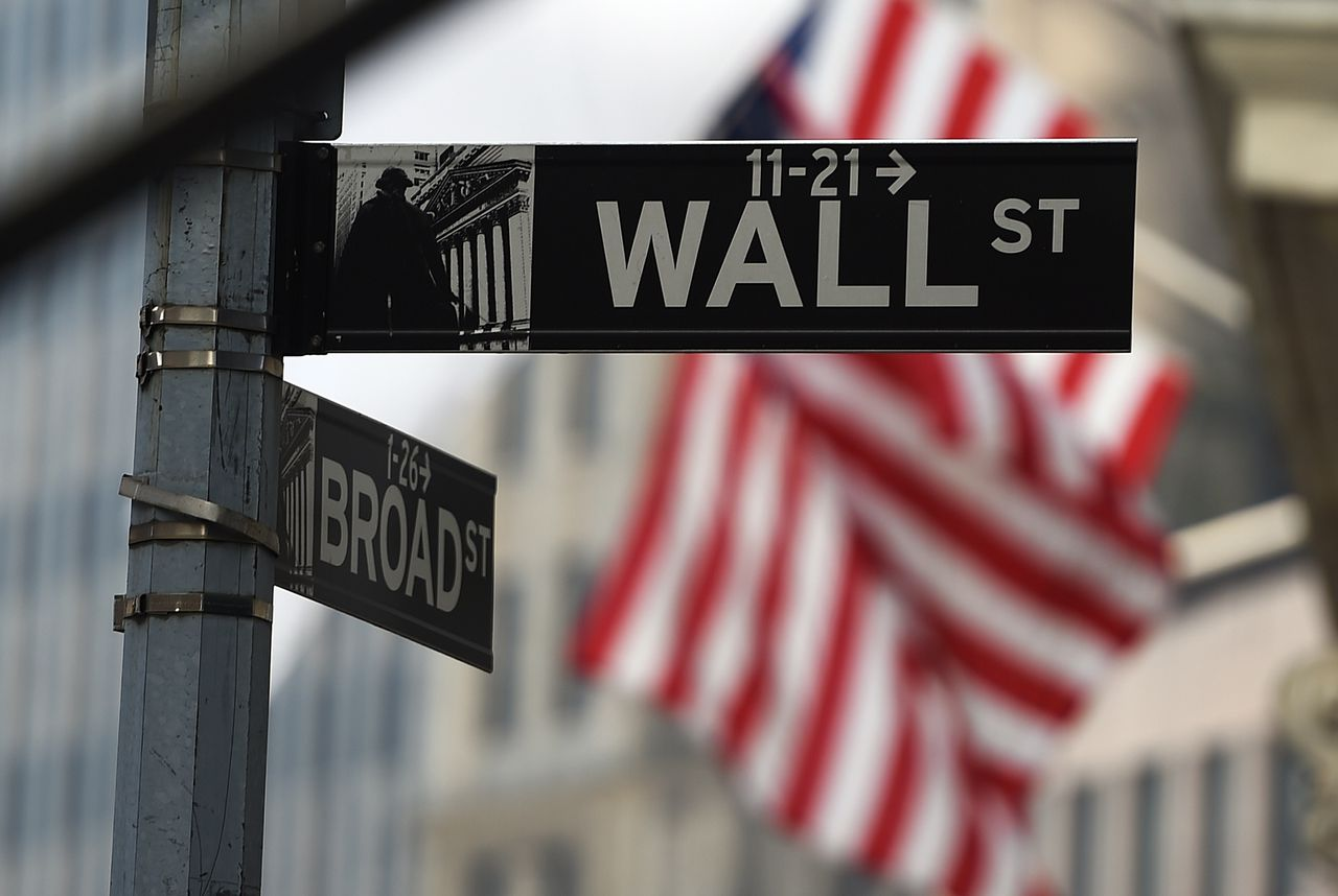 (FILES) This October 16, 2014 file photo shows a Wall Street road sign near the New York Stock Exchange (NYSE) building on in New York. Wall Street stocks retreated from record highs in early trade November 7, 2014 after the Department of Labor reported the US economy added 214,000 jobs in October. About 40 minutes into trade, the Dow Jones Industrial Average stood at 17,522.68, down 31.79 points (0.18 percent), while the broad-based S&P 500 shed 2.05 (0.10 percent) at 2,029.16. Both the Dow and the S&P 500 closed at records Thursday. The tech-rich Nasdaq Composite Index fell 19.79 (0.43 percent) to 4,618.67. The October jobs count came in below the 235,000 expected by analysts. AFP PHOTO/Jewel Samad