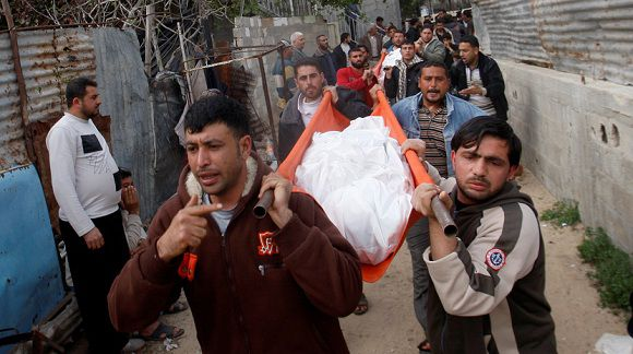 Caption: Palestinians carry the body of Faiza al-Hasoma, 30, killed in an Israeli air strike during her funeral in Beit Lahiya, northern Gaza Strip, Monday, March 12, 2012. The cross-border violence, touched off by Israel's killing of a top militant leader on Friday, has been the worst exchange of fire between Israel and the Hamas-ruled territory in months. (AP photo/Hatem Moussa)