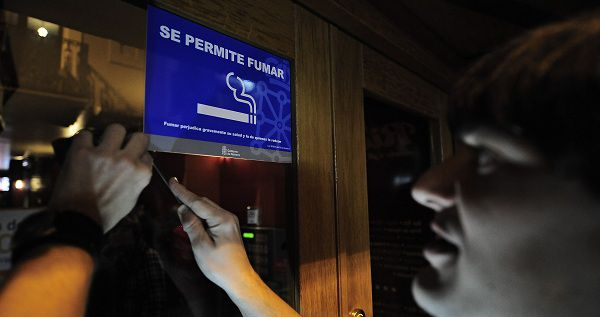 Robert, the owner of a bar, removed with a knife of the window the banner reading: 'Smoking is Allowed' at his bar in Pamplona, Spain, Sunday, Jan.2, 2011. Spain, a country famed for its smoke-filled bars, corner cafes and restaurants, is poised to enact a tough new anti-smoking law eliminating its status as Western Europe's last country where lighting up in indoor public places is allowed until today on January 2. (AP Photo/Alvaro Barrientos)