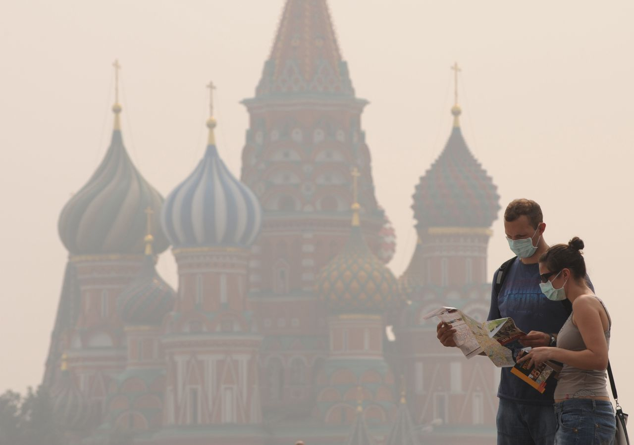 Het Kremlin en de daarnaast gelegen Sint-Basil kathedraal (op de foto) waren gisteren en vandaag gehuld in rook door de branden rond Moskou. Foto AFP People wear face masks to protect themselves from the forest fire smog near St. Basil's cathedral on Red Square in Moscow on August 4, 2010. The death toll from the wildfires that have ravaged Russia has risen to 48, the emergencies ministry on August 4, adding that over 400 new fires were recorded in the last 24 hours. AFP PHOTO / NATALIA KOLESNIKOVA