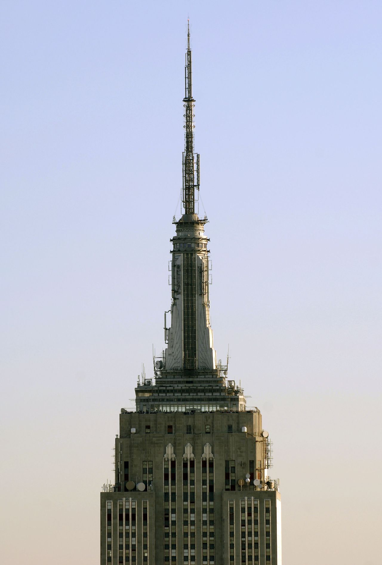 The dirigible mooring mast (unused) and radio antenna atop the 102-floor Empire State Building at sunset, 28 April, 2006, in New York. 01 May, 2006 marks the 75th anniversary of the opening of the 1,454 foot (443.2 meter to the top of the lightning rod) building. Built of steel and aluminum and faced with granite and Indiana limestone, it was for 40 years the world's tallest edifice until surpassed in 1972 by the World Trade Center. It again became the city's tallest after airliners flown by terrorist hijackers destroyed the 110-story twin towers on September 11, 2001. It now ranks ninth in the world, and second in the United States behind Chicago's Sears Tower. AFP PHOTO/Stan HONDA