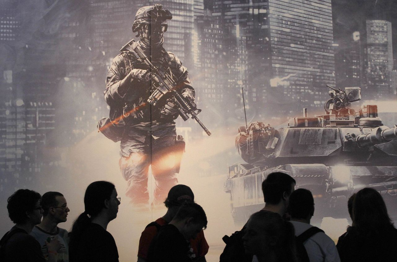 """Visitors stand in front of the """"Batttlefield 3'' exhibition stand during the Gamescom 2011 fair in Cologne August 18, 2011. The Gamescom convention, Europe's largest video games trade fair, runs from August 17 to August 21. REUTERS/Ina Fassbender (GERMANY - Tags: SOCIETY BUSINESS)"""