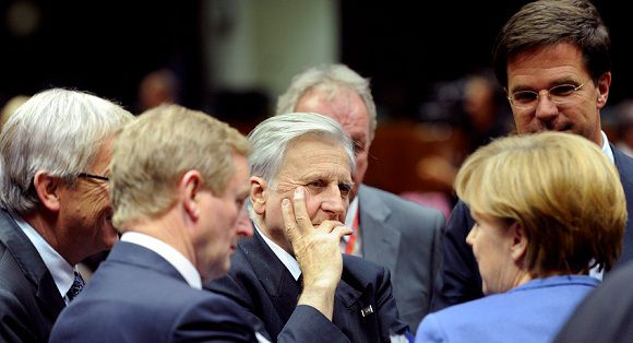 Caption: German Chancellor Angela Merkel, right, speaks with, from left to right, Luxembourg's Prime Minister Jean-Claude Juncker, Irish Prime Minister Enda Kenny, European Central Bank President Jean-Claude Trichet and Dutch Prime Minister Mark Rutte during a roundtable meeting of eurozone members at an EU summit in Brussels on Sunday, Oct. 23, 2011. Greece's prime minister is pleading with European leaders in Brussels to act decisively to solve the continent's debt crisis. At a summit Sunday, the leaders are expected to ask banks to accept huge losses on Greek bonds to ease the pressure on the country, and to raise billions more in capital to weather those losses. (AP Photo/Geert Vanden Wijngaert)