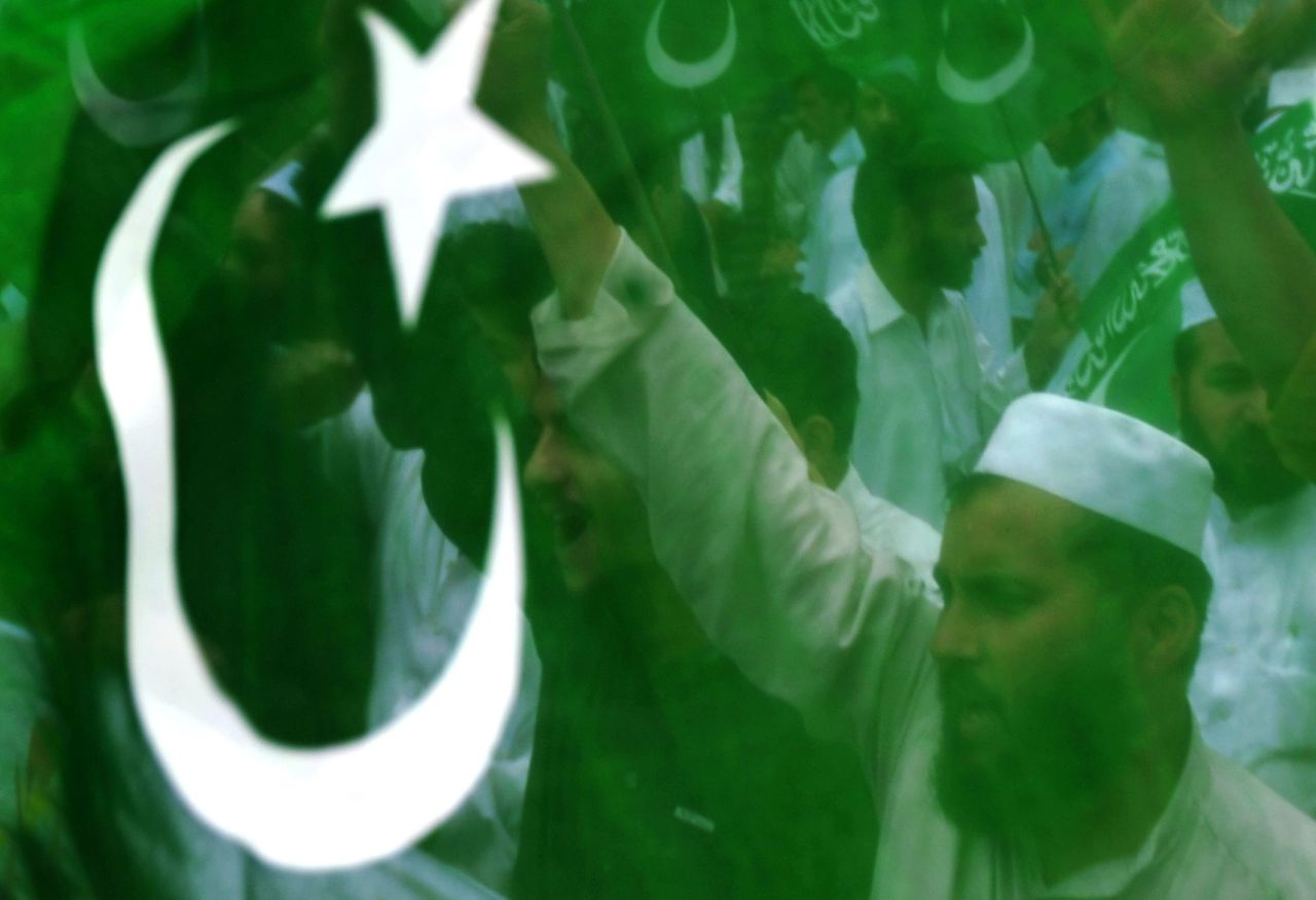 """Activisten van de fundamentalistische Jamaat demonstreren op 6 mei jongstleden in Peshawar tegen Amerika n.a.v. de dood van Osama bin Laden. Foto AFP Behind a Pakistani flag activists of Jamaat-e-Islami Pakistan chant slogans as they march during an anti-US protest on May 6, 2011 in Peshawar condemning the US operation in Pakistan which killed bin Laden on May 1. Hundreds of Pakistanis took to the streets on May 6, cheering Osama bin Laden and shouting """"death to America"""" to condemn a unilateral US raid on their soil that killed the Al-Qaeda chief. Friday is a traditional day of protest in the Muslim world, where demonstrations frequently take place after the main weekly prayers. AFP PHOTO/A MAJEED"""