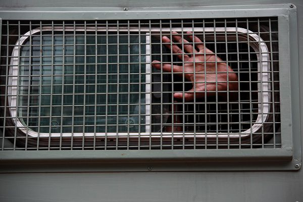 """One of the 45 human rights activists arrested with Munyaradzi Gwisai, a former member of Parliament in Zimbabwe, sticks his hand out from a prison truck after been remanded in custody to the 28th of May together with 45 other social and human rights activists in Harare, Thursday,Feb,24, 2011. Gwisai is alleged to have organized a meeting where they played video footage of the Egypt uprising allegedly """"to inspire and motivate people to demonstrate against the government"""". Police say attendees called for solidarity with Egyptian and Tunisian workers and intended to incite Zimbabweans to hold demonstrations against three decades of authoritarian rule by President Robert Mugabe.(AP Photo/Tsvangirayi Mukwazhi)"""
