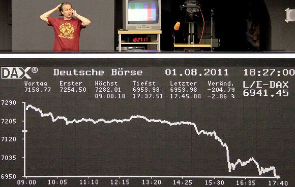 Caption: A man talks on the phone as he stand on the balcony above the DAX board at the Frankfurt stock exchange on August 1, 2011. REUTERS/Remote/Pawel Kopczynski (GERMANY - Tags: BUSINESS)