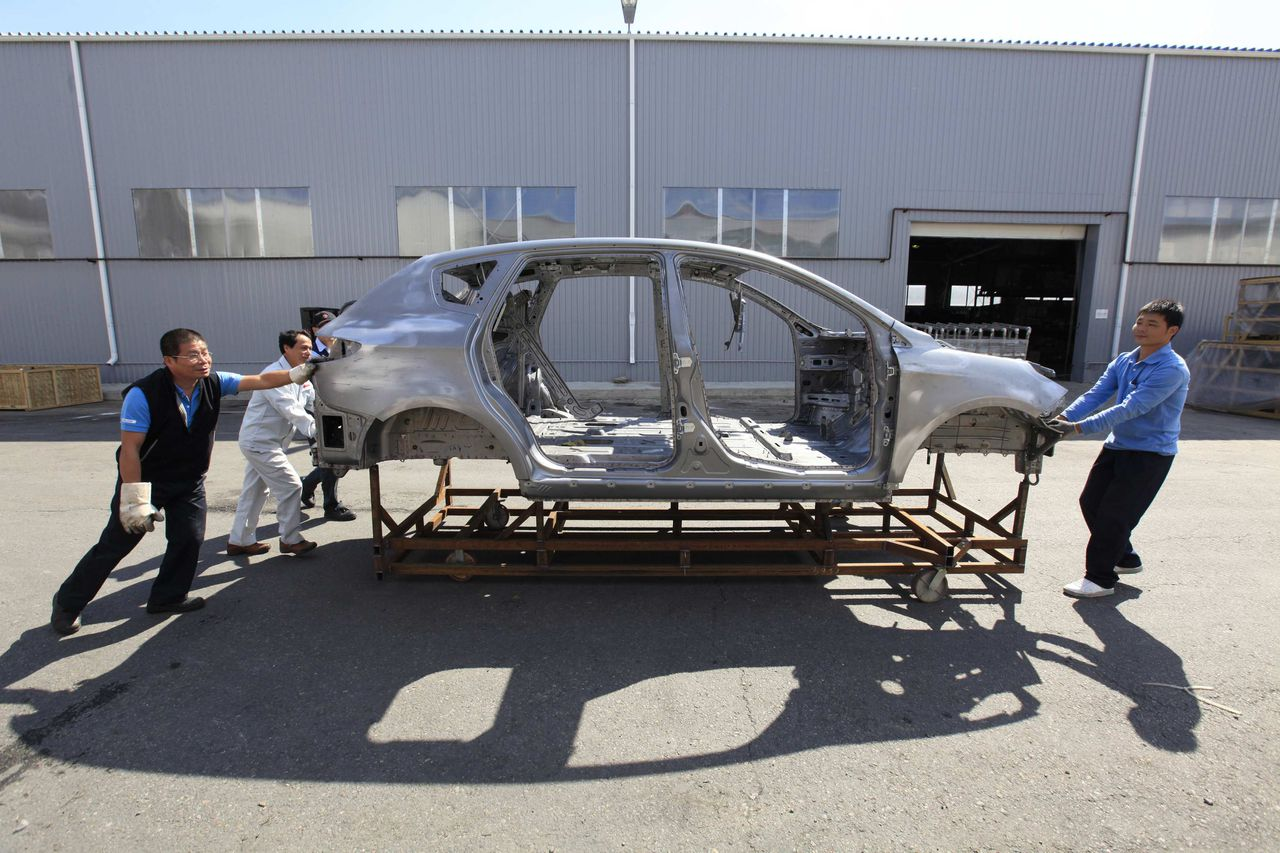 Workers move a car body to a production line at the Derways factory in the city of Cherkessk, some 140km (87 miles) from Stavropol in southern Russia September 7, 2011. The factory assembles some 50,000 automobiles by Chinese manufacturers Lifan and Geely every year. REUTERS/Eduard Korniyenko (RUSSIA - Tags: TRANSPORT BUSINESS)