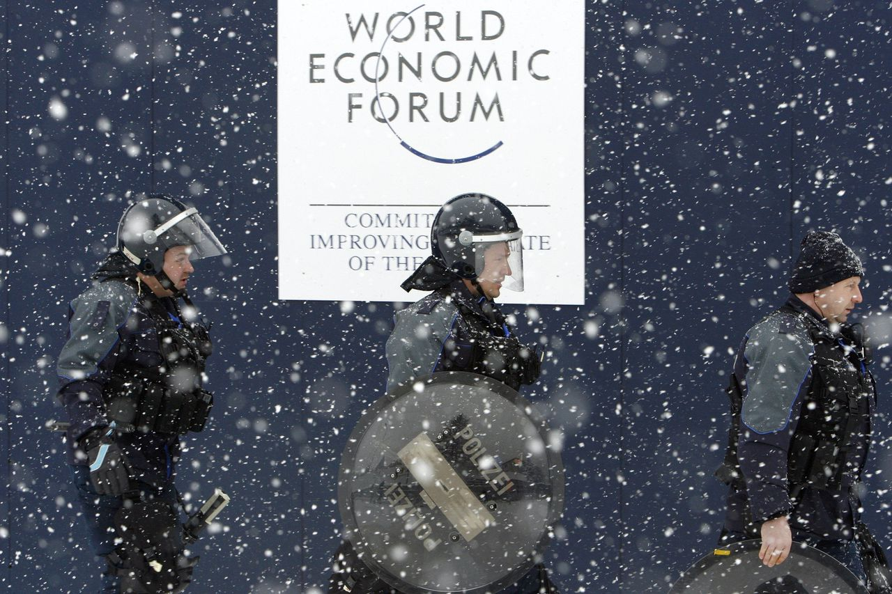 Politiemannen bewaken het congrescentrum van Davos, waar afgelopen week zo'n 2.000 bestuurders van bedrijven en politici bijeen waren voor het jaarlijkse World Economic Forum. Net als in voorgaande jaren trok het congres demonstraties van antiglobalisten aan. Foto AP Riot police patrol next to the Davos Congress Center, during the annual meeting of the World Economic Forum (WEF) in Davos, Switzerland, Saturday, Jan. 27, 2007. (AP Photo/Keystone, Laurent Gillieron)