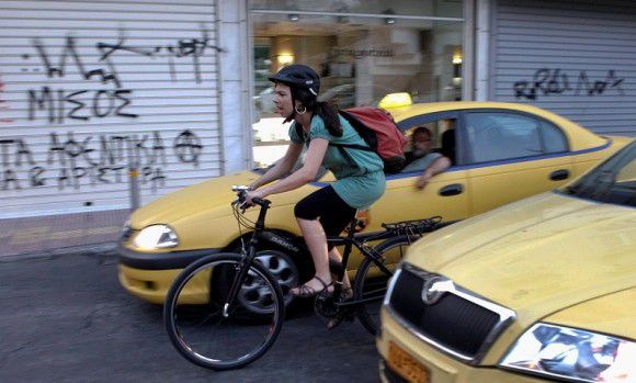 Caption: Music saleswoman Elena Koniaraki, 39, rides her bicycle between taxis at a central street in Athens July 10, 2012. In austerity Greece, the once lowly bike is winning new fans every day, from middle-aged commuters who relied on their cars to those who poked fun at former Prime minister George Papandreou's perchant for cycling as not being macho enough. Picture taken July 10, 2012. REUTERS/Yorgos Karahalis (GREECE - Tags: SOCIETY TRANSPORT BUSINESS)