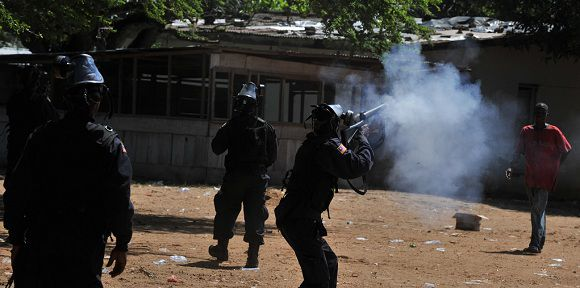 Caption: Liberia police fire at the Congress for Democratic Change headquarters (CDC) in Monrovia on November 7, 2011. Liberian police and protestors exchanged gunfire Monday as a mass opposition rally on the eve of a disputed presidential election run-off turned violent. At least one person was killed Monday during an opposition rally in the Liberian capital that turned violent on the eve of a disputed presidential election run-off. The body of a young man aged around 20 with a gunshot wound to the head was seen by journalists in the offices of the opposition Congress for Democratic Change headquarters, outside which protestors clashed with police. AFP PHOTO / ISSOUF SANOGO