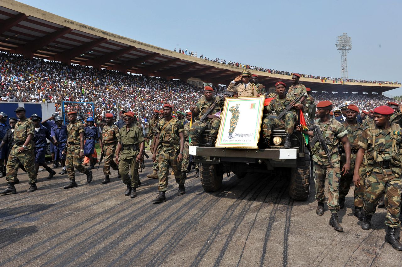 """Begrafenis van dictator Lansana Conté in de Guinese hoofdstad Conakry op 26 december 2008. Foto AFP Guinean soldiers escort the remains of late dictator Lansana Conte arriving at the stadium from the """"Palais du Peuple"""" (people's palace) during his funeral ceremony in Conakry on December 26, 2008. Guinea paid its final respects today to late dictator Lansana Conte as the military junta that seized control in the wake of his death planned a charm offensive to gain international legitimacy. Supporters and even critics of the veteran strongman, who also took power in a coup and ruled for 24 years, were among thousands taking part in funeral ceremonies in Conakry. AFP PHOTO / SEYLLOU"""