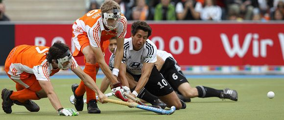 Caption: Jan-Marco Montag (R) of Germany is tackled by Wouter Jolie (L) and Tim Jenniskens (C) of the Netherlands during their final field hockey match at the men's EuroHockey Championships in Moenchengladbach August 28, 2011. REUTERS/Alex Domanski (GERMANY - Tags: SPORT FIELD HOCKEY)