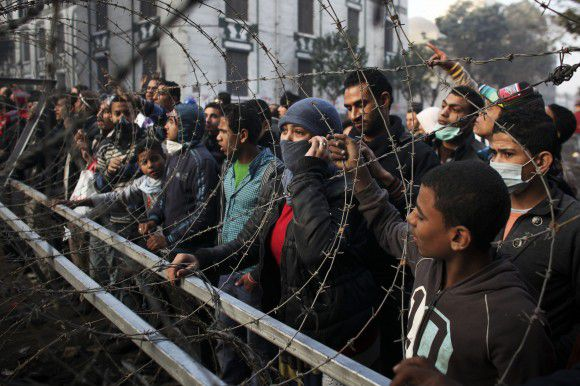 Protesters gather behind a barbed wire barricade, newly erected by the Egyptian army, near Tahrir Square in Cairo, Egypt, Thursday, Nov. 24, 2011. International criticism of Egypt's military rulers is mounting after five days of clashes between police and protesters demanding the generals relinquish power immediately. (AP Photo/Tara Todras-Whitehill)