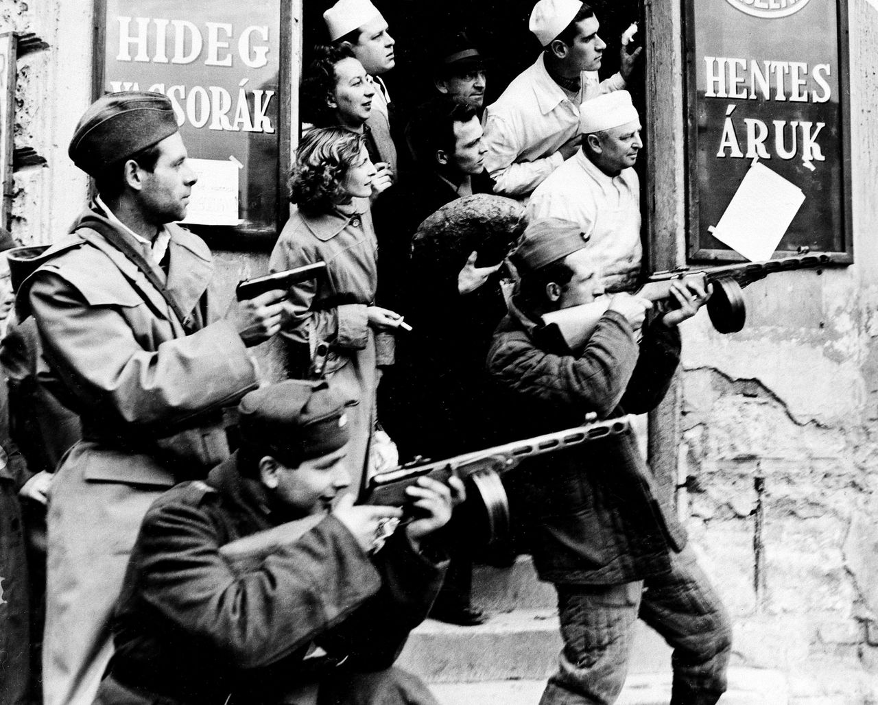 Tijdens de Hongaarse opstand in 1956 beschieten opstandelingen het gebouw van de machtige en gehate geheime politie. Foto AP ** FILE ** Patrons and clerks at a local store look on as members of the Hungarian revolutionary forces take aim at Communist secret police officers, in Budapest, Hungary, in this Nov. 2, 1956 file photo. The uprising began on Oct. 23, 1956 with demonstrations against the Stalinist regime in Budapest and was crushed eleven days later by Soviet tanks amid bitter fighting. Some 2,500 people were killed and a further 200,000 forced into exile. (AP Photo/File)