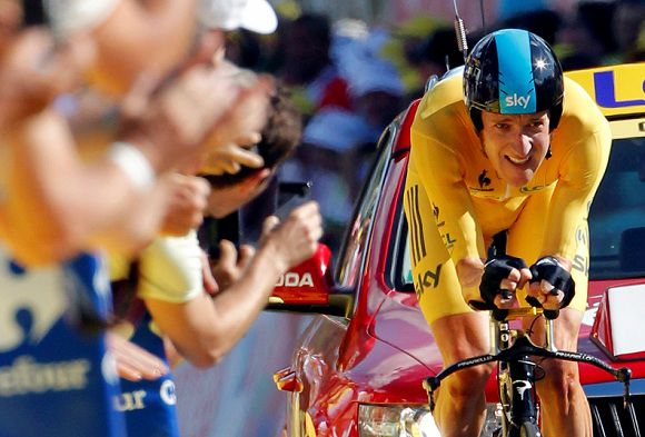 Caption: Team Sky rider and leader's yellow jersey Bradley Wiggins of Britain crosses the finish line during the individual time trial in the ninth stage of the 99th Tour de France cycling race between Arc et Senans and Besancon, July 9, 2012. REUTERS/Stephane Mahe (FRANCE - Tags: SPORT CYCLING)