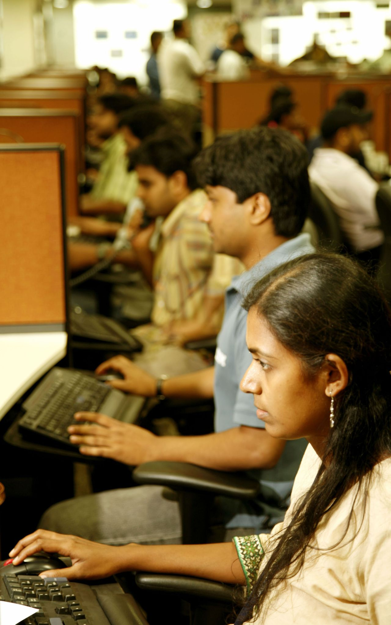 Indiase ICT'ers van IBM. Het Amerikaanse bedrijf is de grootste buitenlandse werkgever van India. Foto Bloomberg Employees work on their ocmputer terminals at IBM in Bangalore, India on Friday, May 19, 2006. IBM, already India's largest foreign employer with 43,000 workers in the country, plans to invest $6 billion by 2009 as the world's largest computer-services company expands operations further. Photographer: Namas Bhojani/Bloomberg News