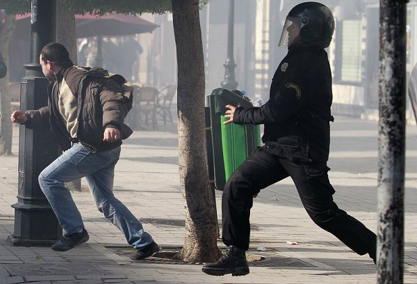 Riot policeman try to catch a demonstrator after police broke up a demonstration in downtown Tunis January 17, 2011. Tunisian security forces used water cannon, tear gas and fired shots in the air on Monday as demonstrators took to the streets demanding that the ruling party of the ousted president give up power. REUTERS/Zohra Bensemra (TUNISIA)