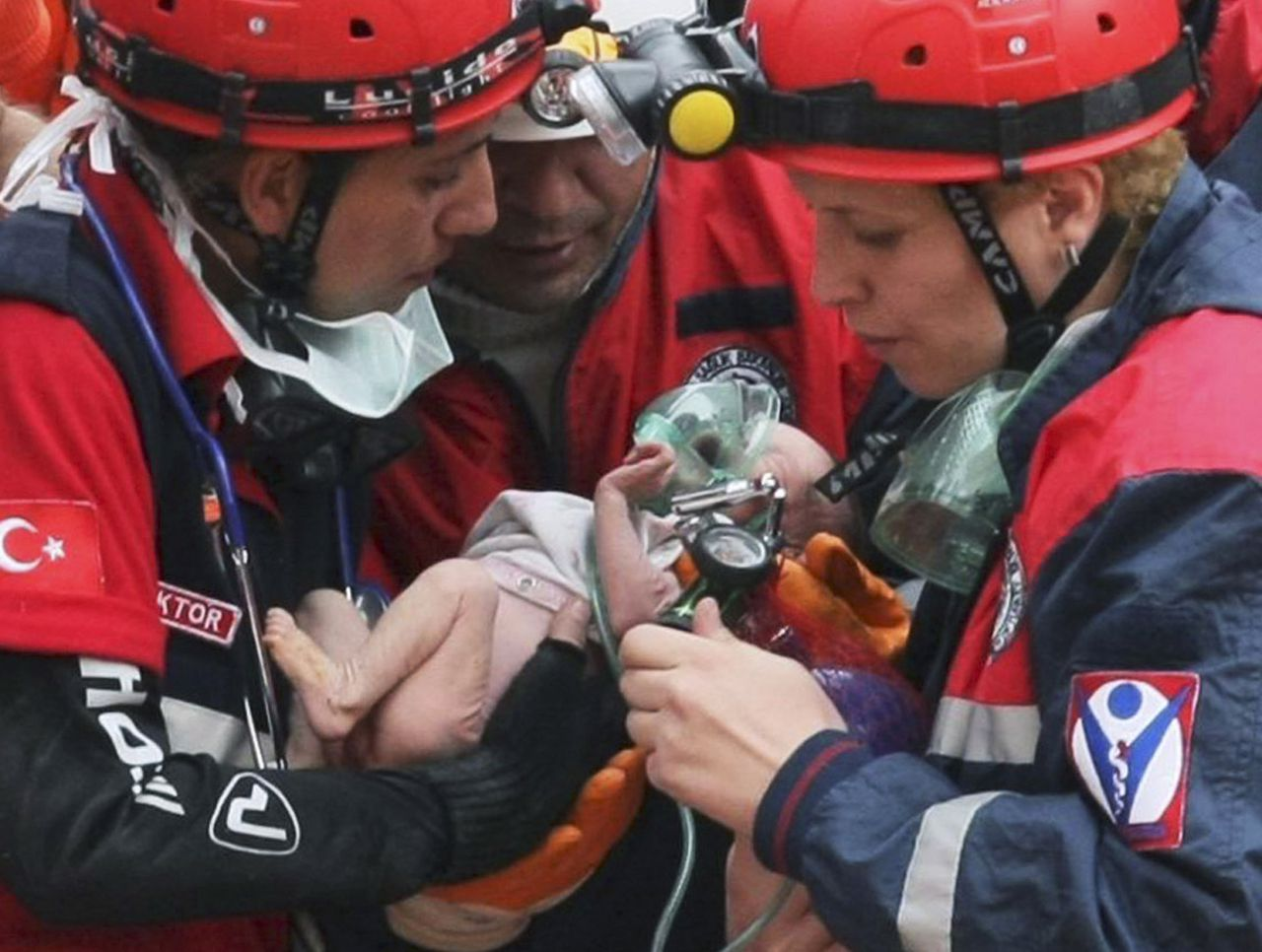 Turkish rescuers carry Azra Karaduman, a two-week-old baby girl they have saved from under debris of a collapsed building in Ercis, Van, eastern Turkey, Tuesday, Oct. 25, 2011. The baby's mother, Semiha, was still alive, pinned next to a sofa inside the flattened building from where the child was rescued. A 7.2-magnitude earthquake toppled some 2,000 buildings in eastern Turkey, Sunday.(AP Photo)