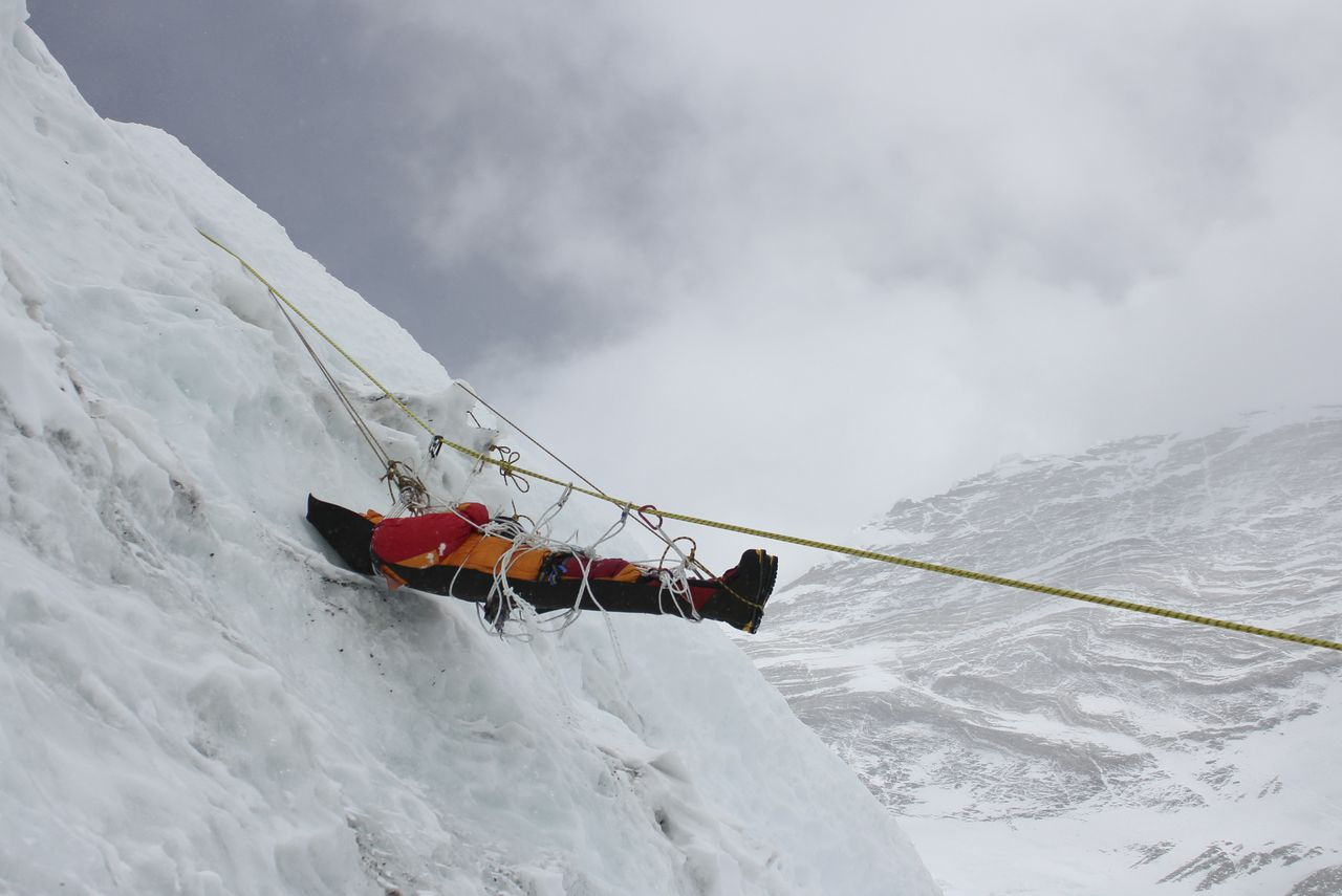 This picture taken on May 16, 2010 a corpse of a mountaineer being retrieved by unseen Nepalese sherpas during the Everest clean-up expedition at Mount Everest. A group of 20 Nepalese climbers, including some top summiteers collected 1,800 kilograms of garbage in a high-risk expedition to clean up the world's highest peak. Led by seven-time summiteer Namgyal Sherpa, the team braved thin air and below freezing temperatures to clear around two tonnes of rubbish left behind by mountaineers, that included empty oxygen cylinders and corpses. Since 1953, there have been some 300 deaths on Everest. Many bodies have been brought down, but those above 8,000 metres have generally been left to the elements -- their bodies preserved by the freezing temperatures. The priority of the sherpas had been to clear rubbish just below the summit area, but coordinator Karki said large quantities of refuse was collected from 8,000 meters and below. AFP PHOTO/Namgyal SHERPA