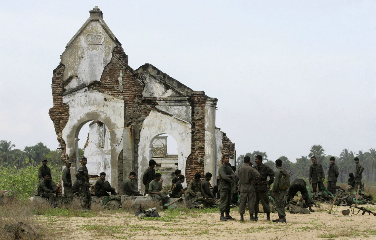 """Militairen bij de restanten van een kerk in Mullaitivu, de laatste grote stad die in handen was van de Tijgers. Het Sri Lankese leger veroverde de stad eerder deze week. (Foto AP) ** ADDS THAT GOVERNMENT DENIED THE ALLEGATION OF CIVILIANS WHO WERE KILLED IN THE FIGHTING ** Sri Lankan Army soldiers are seen outside a damaged church in the newly recaptured Tamil rebel held town of Mullaittivu, about 230 kilometers (143 miles) northeast of Colombo, Sri Lanka, Tuesday, Jan. 27, 2009. At least 300 civilians were wounded and scores feared killed by Sri Lankan army artillery shells fired into a designated """"safe zone"""" for ethnic Tamils trapped by fighting between the military and Tamil rebels, a health official alleged Tuesday. Sri Lankan Army and government have denied the allegation of civilians getting killed during the fighting between military and Tamil rebels. (AP Photo/Gemunu Amarasinghe)"""