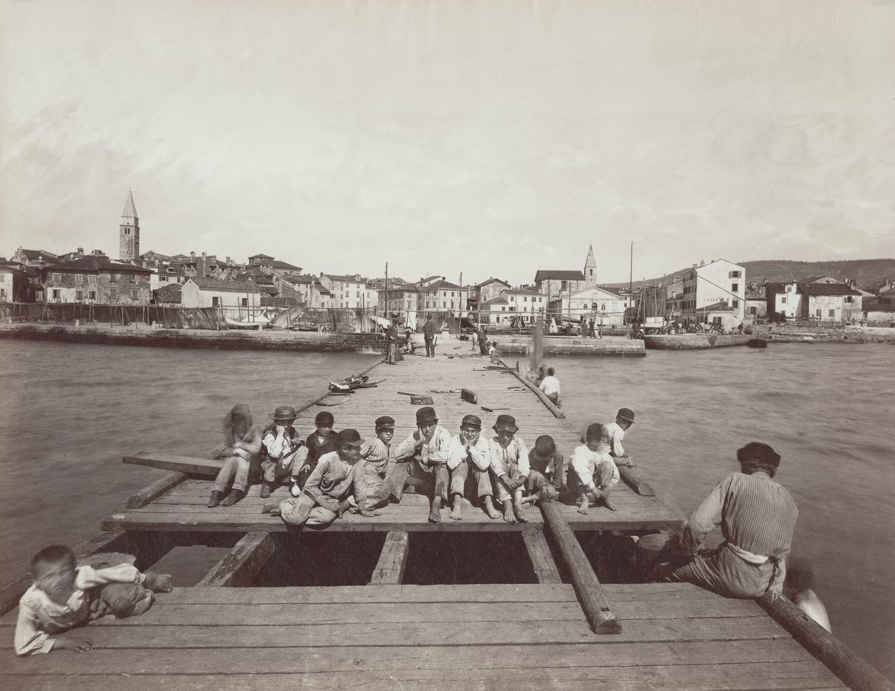 ca. 1890, Izola --- Boys relax on a pier in the town of Izola, on the Istria Peninsula, then under the rule of the Austria-Hungary. --- Image by © Alinari Archives/CORBIS