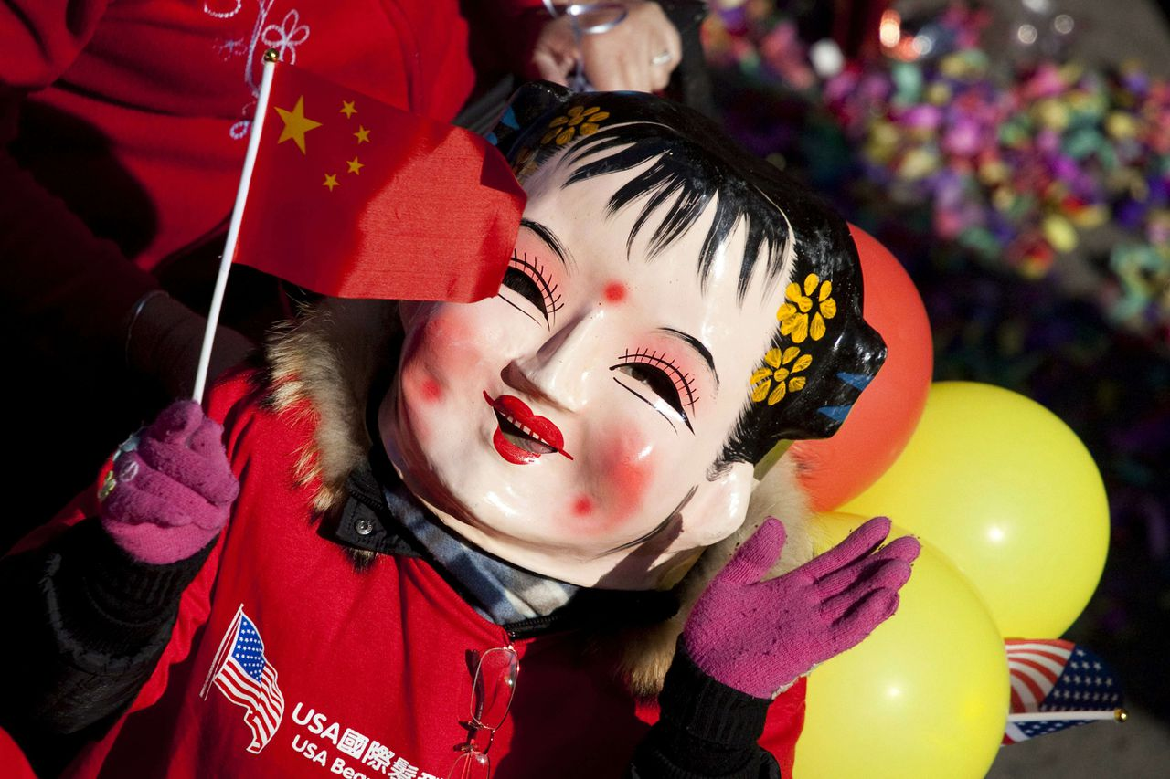 NEW YORK, NY - FEBRUARY 06: A participant in the 12th Annual Chinatown Lunar New Year Parade waves a Chinese flag on February 06, 2011 in New York City. The year of the rabbit began on February 3. Michael Nagle/Getty Images/AFP == FOR NEWSPAPERS, INTERNET, TELCOS & TELEVISION USE ONLY ==