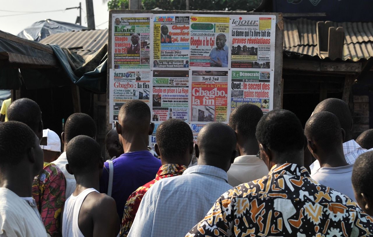 People check local newspapers bearing pictures of ex-Ivorian president Laurent Gbagbo in the Abobo neighborhood of Abidjan on November 30, 2011 a day after the transfer of Gbagbo to The Hague. The former Ivorian president was transferred from northern Ivory Coast by charted plane to the Hague-based ICC's detention facility early on November 30, where he is to face four counts of crimes against humanity for his role in the bloody aftermath of disputed presidential polls last year. AFP PHOTO / ISSOUF SANOGO