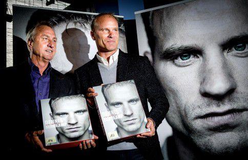 Dennis Bergkamp overhandigt het eerste exemplaar van zijn biografie aan Johan Cruijff tijdens de presentatie in Amsterdam.