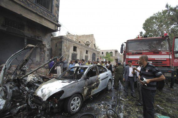 People stand near burnt cars after a car bomb explosion in Sanaa September 11, 2012. The car bomb targeting Yemeni Defence Minister Major General Muhammad Nasir Ahmad exploded outside the prime minister's office in Sanaa on Tuesday, killing at least five bodyguards but the minister was safe, government sources said. REUTERS/Mohamed al-Sayaghi (YEMEN - Tags: POLITICS CIVIL UNREST)