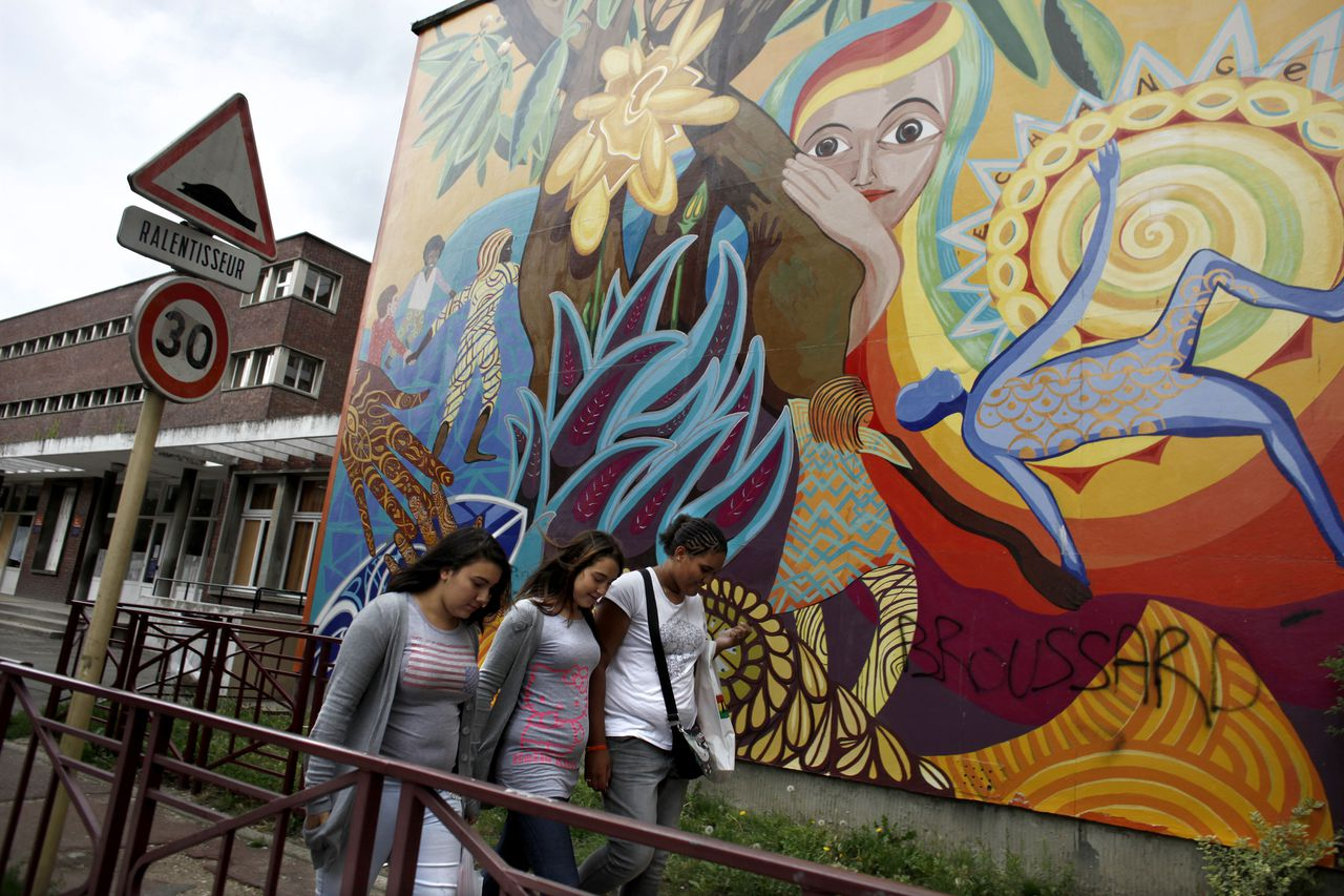 Women walk past a mural painted outside a school in Bondy, a multiracial Paris suburb, on Aug. 28, 2010. The U.S. Embassy in Paris has formed a network of partnerships with local governments, advocacy groups, entrepreneurs, students and cultural leaders in the troubled immigrant enclaves outside France's major cities. ( Corentin Fohlen/The New York Times)
