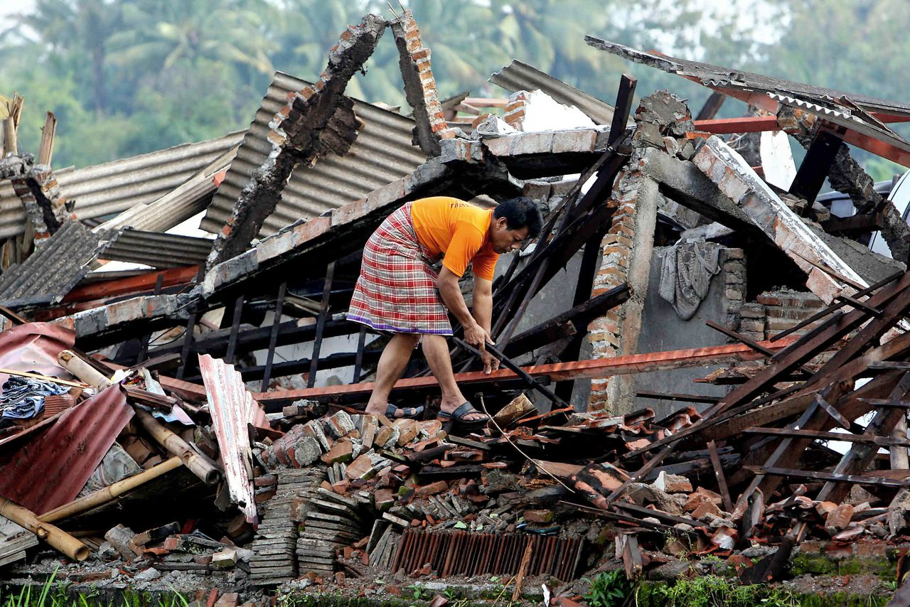 Een inwoner van Bantul, waar ruim 2.000 inwoners zijn omgekomen, zoekt tussen de resten van ingestorte huizen naar zijn bezittingen Foto AFP A resident searches belongings amongst the rubbles of his destroyed house in Bantul Yogyakarta, 28 May 2006, a day after a devastating earthquake shattered the region. As dawn broke over Indonesia's city of Yogyakarta, rescue workers searched for survivors of the 6.2 magnitude quake that killed at least 3,000 people. With whole villages reduced to rubble, the death toll was expected to rise as countless victims lie dead or injured, trapped in the wreckage of their homes, after the nation's worst catastrophe since the 2004 Asian tsunami. AFP PHOTO/Jewel SAMAD