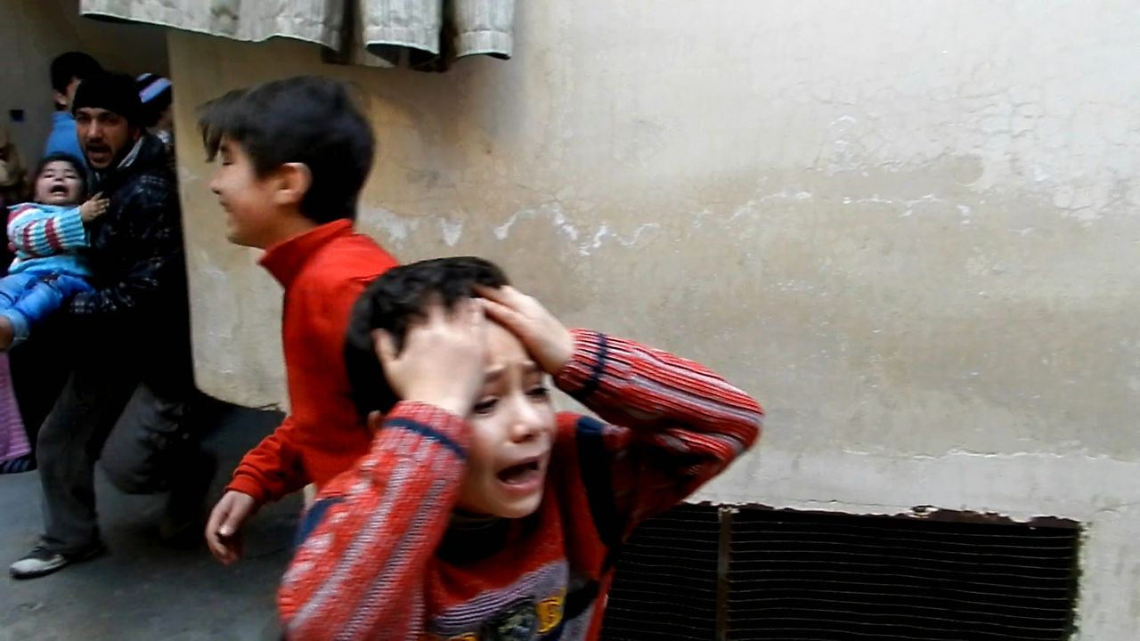 A man (L) runs carrying a toddler as children weep during fighting in the Bab Tudmor neighborhood of the restive city of Homs, some 160kms north of the Syrian capital Damascus on February 25, 2012. China called for an end to violence in Syria on March 4, 2012, as the regime of Bashar al-Assad sparked international outrage by blocking aid from reaching the battered Baba Amr flashpoint in Homs city. AFP PHOTO/STR