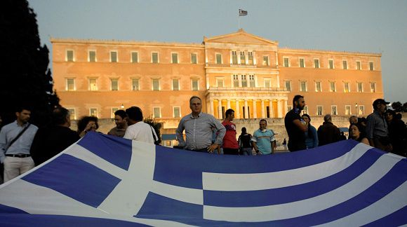 Caption: Protesters hold a Greek flag during a rally against austerity in front of the parliament in Athens September 27, 2011. The Greek parliament is expected to approve a deeply unpopular property tax on Tuesday to lure international lending inspectors back to Athens and release vital aid, even as demonstrators stepped up protests against more austerity. REUTERS/John Kolesidis (GREECE - Tags: POLITICS BUSINESS CIVIL UNREST)