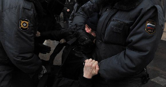 Caption: Police officers detain an opposition activist outside the area of an authorized opposition protest against the alleging mass fraud in the December 4 parliamentary polls in central St.Petersburg, on December 10, 2011. Tens of thousands of election protesters turned out today in Moscow and other major cities across Russia in open defiance to strongman Vladimir Putin's 12-year rule. AFP PHOTO / OLGA MALTSEVA