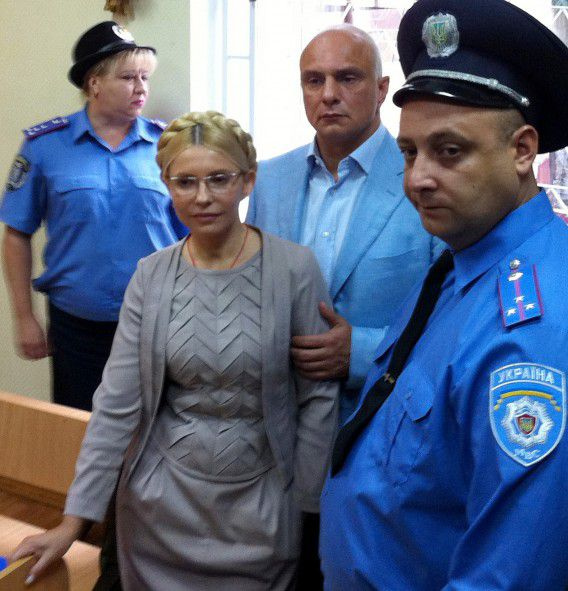 """(FILES) A file photo taken on August 11, 2011 shows Former Ukrainian Prime Minister Yulia Tymoshenko (C) inside a courtroom in Kiev. The judge in her trial, Rodion Kireyev, said in the verdict on October 11 that Tymoshenko clearly had exceeded her authority in signing a gas deal with Russia in 2009 and used her powers to """"criminal ends"""". Kireyev has yet to announce his final judgement in the case or give any details on sentencing if the former Orange Revolution leader is found guilty in the case. AFP PHOTO/ POOL / ALEXANDER PROKOPENKO"""