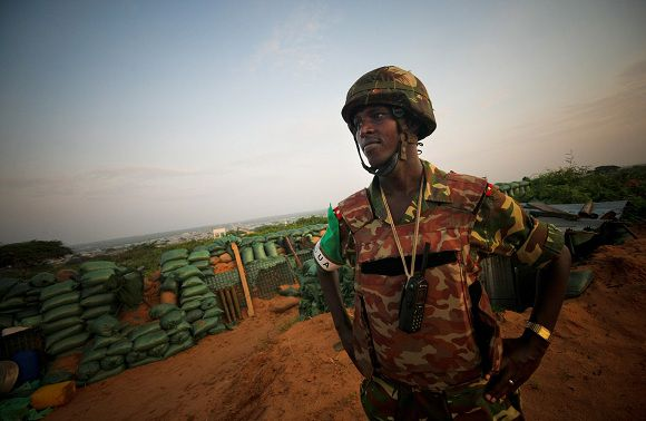 In this photo released by the African Union-United Nations Information Support Team (AU-UN IST) on Saturday, Nov. 19, 2011, a Burundian commander serving with the African Union Mission in Somalia (AMISOM) stands just after sunrise along frontline defensive positions in territory recently captured from insurgents in Deynile District along the northern fringes of the capital Mogadishu, Somalia on Friday, Nov. 18, 2011. (AP Photo/AU-UN IST, Stuart Price)